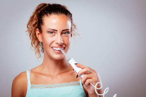 woman using a water flosser to clean teeth